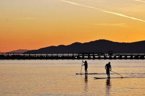 Stand up paddle boarding is both a great core workout and a relaxing way to enjoy the beauty of the water.  Here are two people enjoying a SUP in English Bay, Vancouver.
